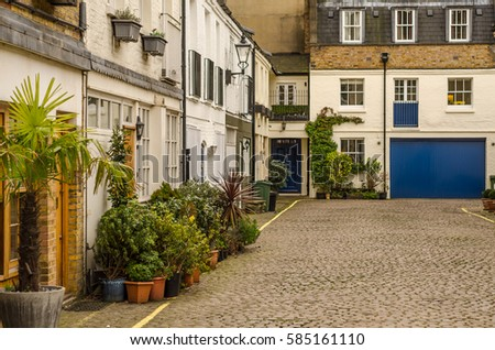 corner of the courtyard in front of the beautiful old buildings in low-rise, on the sidewalk exotic potted plants, stylish street lamps, paving stones on the road, urban architecture