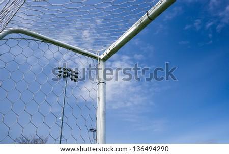 Corner of the soccer gate against blue sky. - stock photo