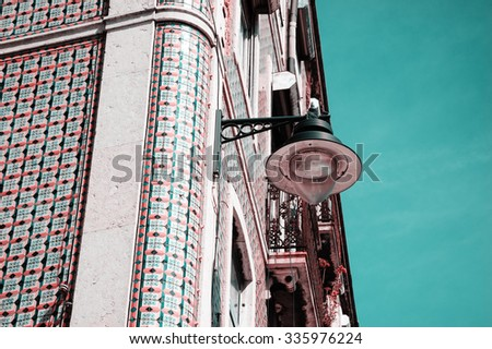 Corner of  typical old building in the centre of Lisbon (Portugal). Colorful  ceramic tiles (azulejos) with geometric pattern and a hanging lantern. Toned photo. - stock photo