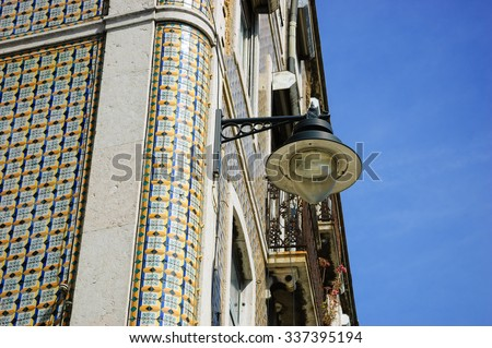 Corner of  typical old building in the centre of Lisbon (Portugal). Colorful  ceramic tiles (azulejos) with geometric pattern and a hanging lantern. - stock photo
