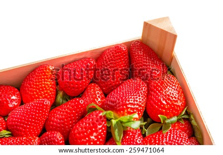 Corner of wooden box of tasty spanish strawberries freshly collected isolated on white background - stock photo