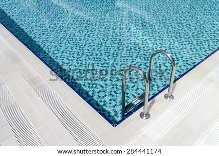 corner view of aluminum swimming pool stairs - stock photo