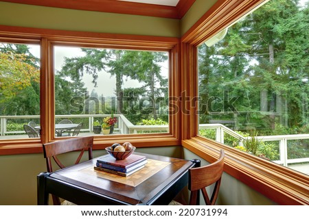 Corner with green walls and brown trim. Furnished with dining table with two chairs - stock photo