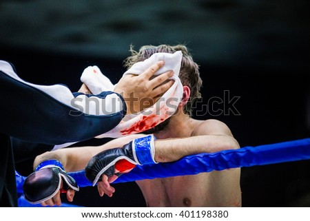 cornerman wipes face of a fighter in between rounds, blood on towel - stock photo
