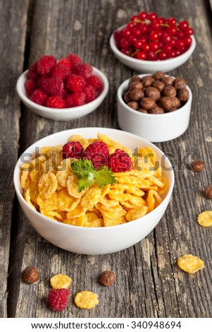 Cornflakes and different Berries, vertical, close up - stock photo