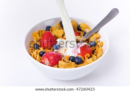 Cornflakes cereal with strawberries and blueberries in a white bowl isolated over white
