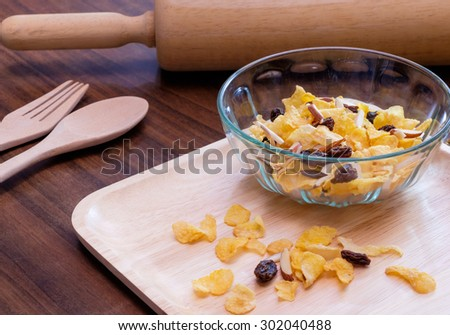 Cornflakes, currant and almond for breakfast with wooden background - stock photo