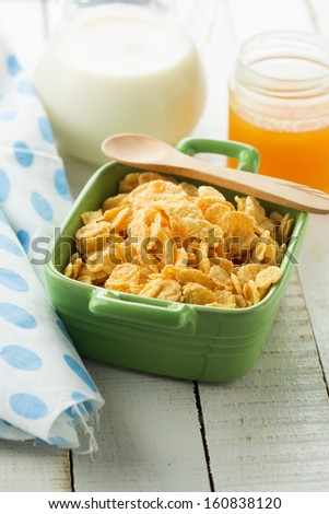 Cornflakes in bowl with milk and honey on wooden background. Selective focus.