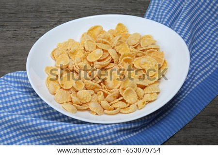 Cornflakes in plate with napkin on wood background