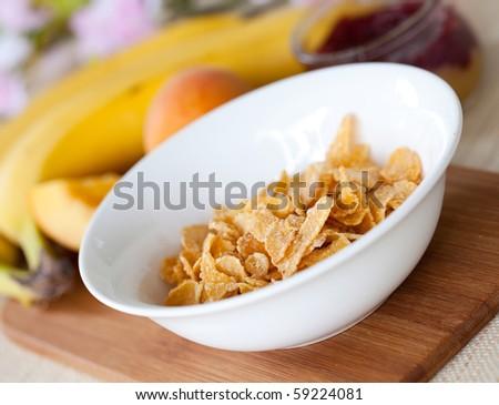 cornflakes in white bowl on table - stock photo