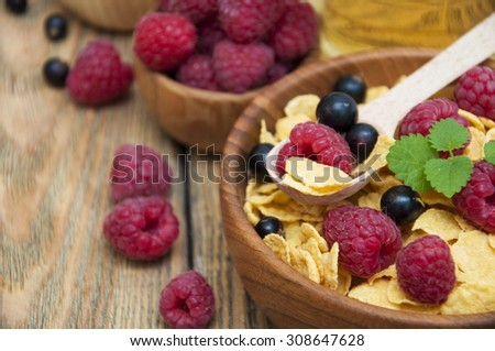Cornflakes with berries raspberries, blueberries and currants with milk and honey on wooden background - stock photo