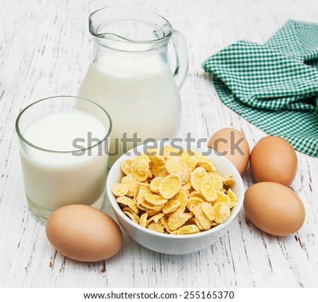 Cornflakes with milk and eggs on a wooden background