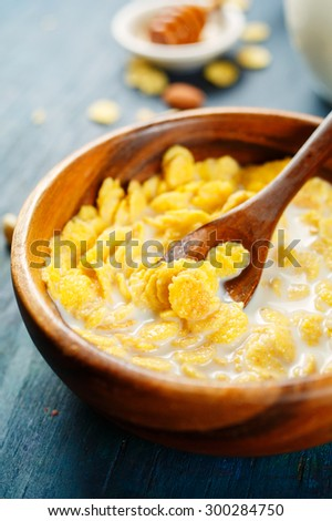Cornflakes with milk in a wooden bowl. Selective focus. - stock photo