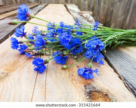 Cornflower on wooden background. Eco flowers. Selective focus, space in the zone blurring compositions for the production of advertising. - stock photo