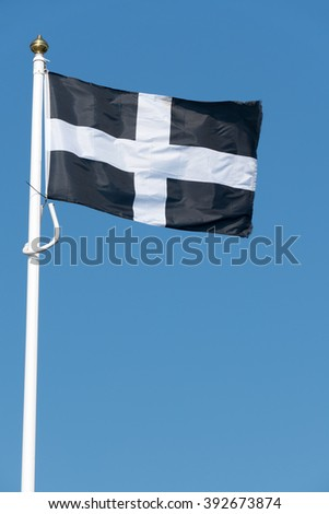 Cornish flag of St. Piran blowing in the wind. - stock photo