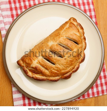 Cornish pasty on a beige plate - stock photo