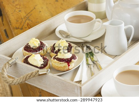 Cornish Tea: home made scones topped with Cornish clotted cream and strawberry jam on a wooden tray