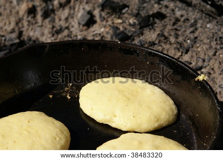 Cornmeal batter being cooked into pancakes in an iron skillet over an open fire - stock photo