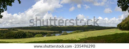 Cornwall countryside,  landscape of hilly lush Cornwall countryside with river flowing among green fields  - stock photo