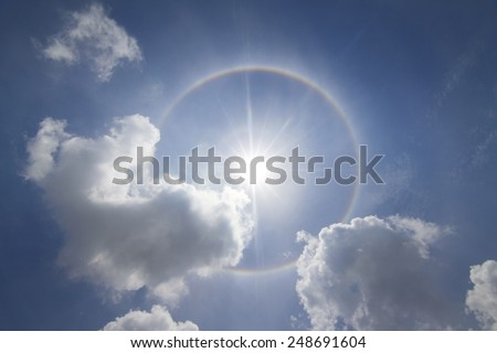 Corona on blue sky, the sun with the ring and flying birds. - stock photo