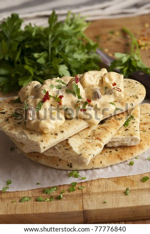 Coronation chicken with warm naan bread on a wooden board - stock photo
