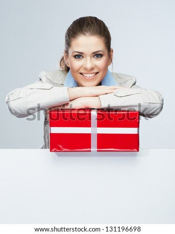 Corporate bonus concept . Smile Business woman hold red gift box, portrait with blank white board on gray isolated . Female smiling model . - stock photo