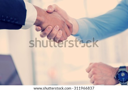 Corporate business handshake. Close-up view of a handshake while two successful businessman shaking hands at the table against each in the business office in formal wear and work at a laptop.