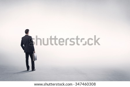 Corporate business male in modern suit standing in big blank empty grey space concept - stock photo