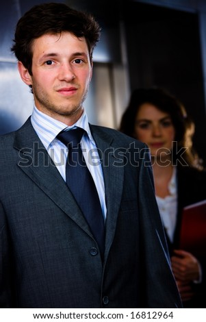Corporate business portrait of businessman with businesswoman in background at office corridor.