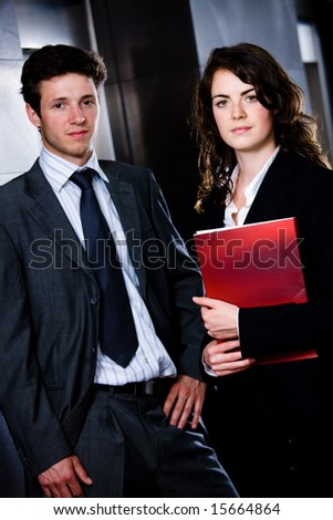 Corporate businesspeople businessman and businesswoman standing side by side posing for team portrait at office corridor.