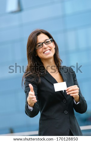 Corporate businesswoman showing white empty business card and giving hand for handshake Successful female hispanic caucasian executive outside. - stock photo