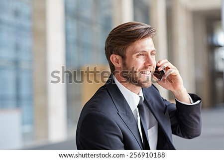 Corporate executive smiling while talking his phone and looking away - stock photo