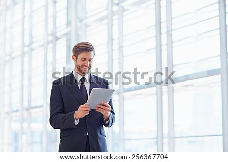 Corporate executive using a digital tablet in a modern architectural setting - stock photo