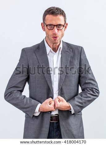 corporate fighter - bossy middle aged manager with eyeglasses ready to loose his temper, impressing with big shoulders and strong fists together, grey background studio