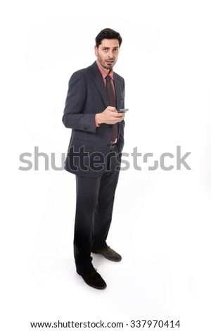 corporate full body portrait of young attractive businessman of Latin Hispanic ethnicity using mobile phone in suit and tie standing isolated on white background