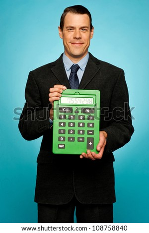 Corporate guy showing big green calculator to camera isolated over gradient background - stock photo