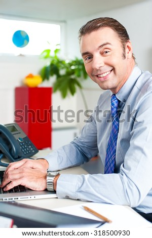 Corporate guy using laptop in office - stock photo