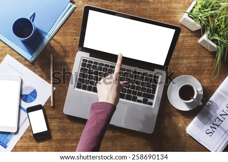 Corporate identity mock up on a wooden desktop with laptop, tablet and smartphone - stock photo
