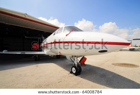 Corporate jet sitting part way in hanger while crews do maintenance inside cockpit and electrical. - stock photo