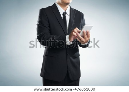 Corporate male executive messaging via phone , with clipping path