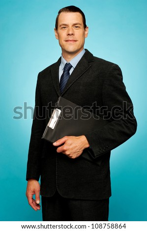 Corporate man holding clipboard and posing. Looking at camera - stock photo