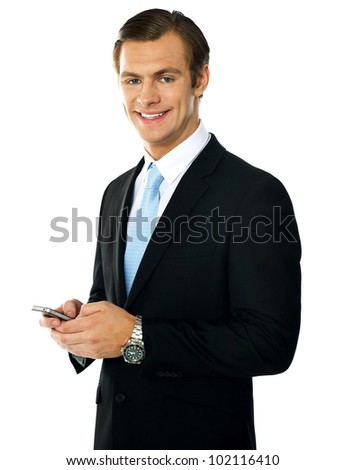 Corporate man messaging from cellphone, smiling at camera