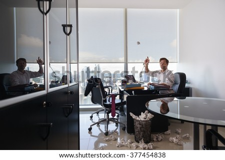 Corporate manager in modern office tries to write a job letter. The man is frustrated and keeps on screwing paper to the garbage bin - stock photo