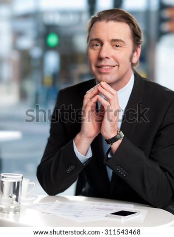 Corporate manager posing to the camera at cafe - stock photo