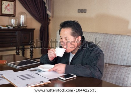 Corporate middle-aged man in a cafe watching reports