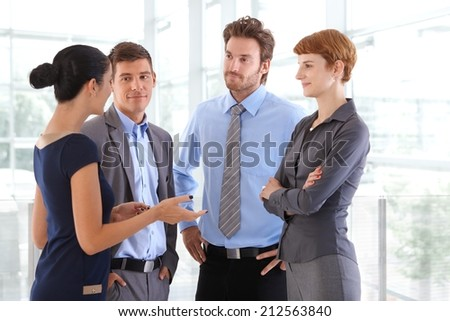 Corporate people chatting at business office lobby. Standing, gesturing, arms crossed, arms on hip, confident, wearing suit, confident.