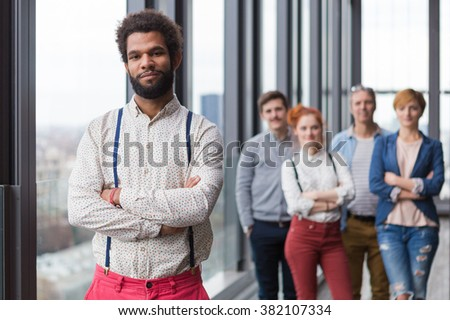 Corporate portrait of young black hipster businessman with his colleagues in background. - stock photo