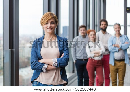 Corporate portrait of young business woman with her colleagues in background. - stock photo