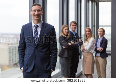 Corporate portrait of young businessman with his colleagues in background.