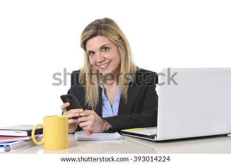 corporate portrait young happy Caucasian blond business woman working using internet on mobile phone at office computer desk smiling confident in successful female executive concept - stock photo